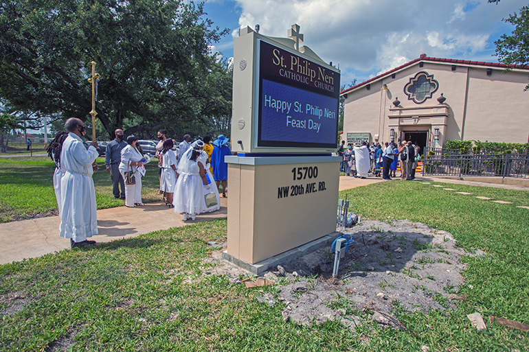St. Philip Neri parishioners gather near their new digital sign for a blessing ceremony on Trinity Sunday, May 30, 2021.