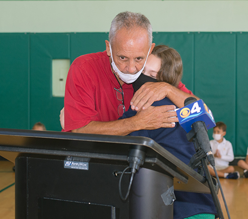 Art Fernandez hugs seventh-grader Olivia Peacock, 12,  after receiving the Key to the City of Miami Beach from Mayor Dan Gelber. Fernandez is retiring after 39 years as physical education teacher at St. Patrick School on Miami Beach.