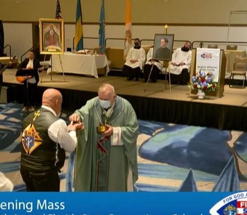 Archbishop Thomas Wenski distributes Communion while celebrating the opening Mass, May 28, 2021, at the state convention of Knights of Columbus in Orlando. The day before, he joined almost 30 Knights on Bikes on a ride from Weston to Kississime to promote vocations on the way to the convention.