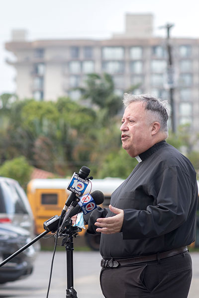 Father Juan Sosa, pastor of St. Joseph Church, Miami Beach, the parish nearest to the collapsed condo building in Surfside, speaks to the media June 25, 2021, 2021. In the distance, the remains of the Champlain Towers South South in Surfside can be seen from the church parking lot.