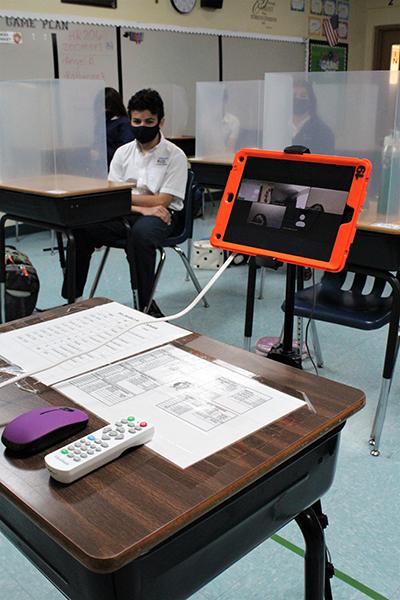 Blindados y protegidos, en persona o virtual: los estudiantes de la Escuela Our Lady of the Lakes sentados en sus escritorios esperan el inicio de la clase. También estaban esperando los estudiantes que asisten a su clase virtualmente, visibles a través de un iPad en frente del salón de clases conectados a través de Zoom.