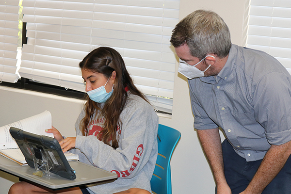 Jena Masri, an eleventh grader, gets some help from her teacher, Brian Dunne, during history lessons. She is back on campus and participating in classes with other students while others stay at home and join the sessions online.