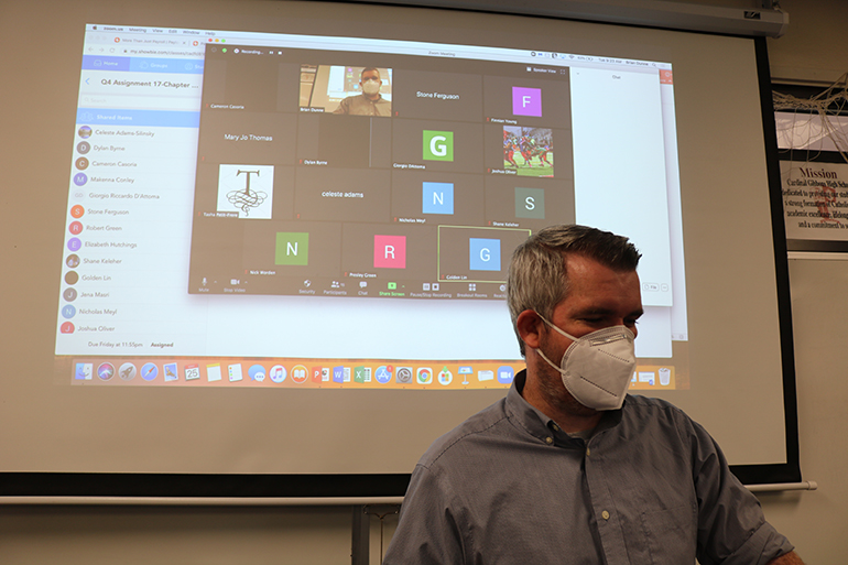 Brian Dunne teaches history to a class of juniors during sessions at Cardinal Gibbons High School May 25, 2021. The screen behind him reveals online students participating in class alongside the students sitting in the classroom.