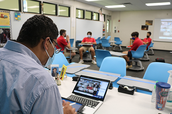 Nelson Araque multitasks and stays constantly busy during his theology class at Cardinal Gibbons High School as he teaches his online and in-person students and tries to keep them engaged and interested.