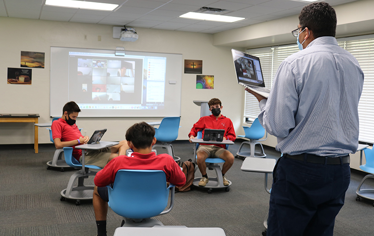 Nelson Araque moves about his classroom talking and asking questions to the students sitting in front of him as well as those connected virtually online. He is busy multitasking through the entire session trying to keep the class interesting and his students engaged.