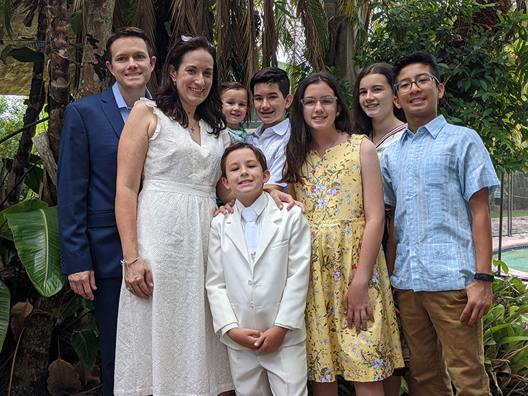 Richard Lopez gathers his family after Mass May 15, 2021 at the Church of the Little Flower in Coral Gables where his son, Nicholas, 8, received the sacrament of holy Communion. Shown standing by him is his wife Angelique and the rest of their children.