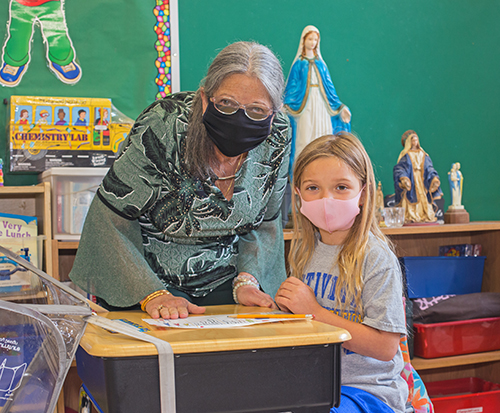 Nativity School kindergarten teacher Margaret Knowles, seen here with student Madeleine Carvajal, 6, is retiring this month, having never missed a day of teaching in 27 years.