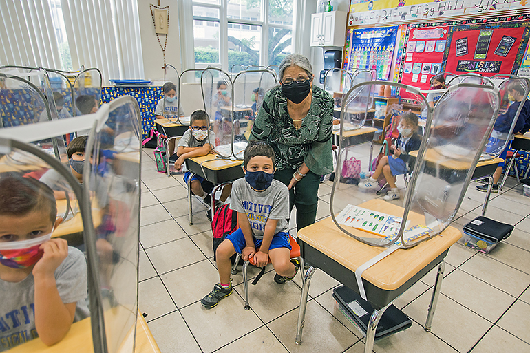 Nativity School kindergarten teacher Margaret Knowles poses with student, James Sayfie, 6, and his classmates before her last day of school. She is retiring this month, having never missed a day of teaching in 27 years.