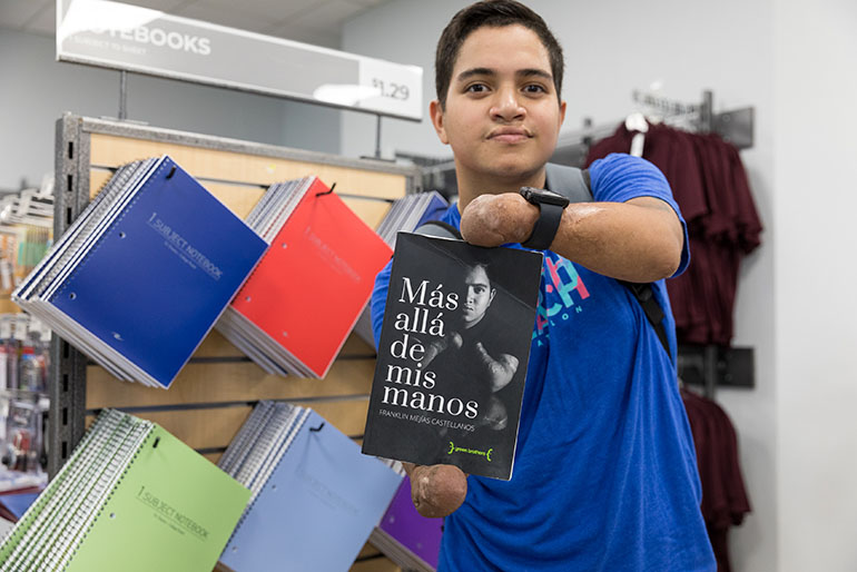 St. Thomas University student Franklin Mejias Castellano, who was left handicapped by an infection acquired during a trip to Florida from his native Venezuela when he was 12, holds a copy of his book, which tells the story of his overcoming the loss of his limbs following the infection.