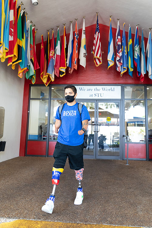 St. Thomas University student Franklin Mejias Castellano, who was left handicapped by an infection acquired during a trip to Florida from his native Venezuela when he was 12, walks through the university campus in May 2021.