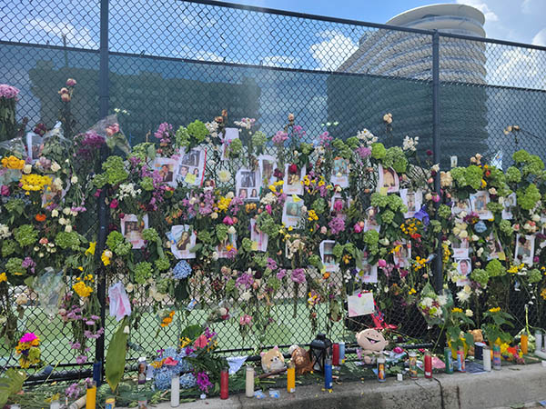 The memorial wall at the tennis court across the Champlain Towers South building collapse is filled with photos of the missing and victims, flowers, candles, rosaries, and more. Some of the toys and stuffed animals placed at the memorial were reportedly recovered from the building collapse site.