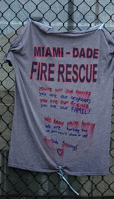 A T-shirt supporting Miami-Dade Fire Rescue and other first responders is left on the memorial wall for those affected by the Champlain Towers South building collapse in Surfside.