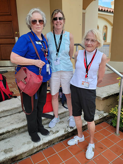 Volunteers from the Red Cross, all retired nurses, take a break from the heat on the steps of St. Joseph Church in Miami Beach on July 1, 2021, during recovery efforts for the Champlain Towers South building collapse. From left: Leslie Roberts, from Austin, Texas, Pat Duncan from Eustis, Florida, and Shirlee Reding from Des Moines, Iowa.