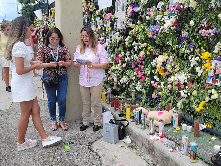 Paola Rendon, Marta Roca, and Jasmira Rendon, members of the Legion of Mary and parishioners of St. Kieran Church in Miami, pray July 2, 2021 at the memorial wall located at the tennis court across the street from the Champlain Towers South building. They placed Miraculous Medals of the Virgin of the Immaculate Conception along the memorial wall. The Legion has been praying for the end of the COVID-19 pandemic, and now for those affected by the building collapse.