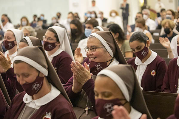 Sister Delia Morales, center, of the Servants of the Pierced Hearts of Jesus and Mary, cheers for Father Joseph Mary during the Mass of his profession of first religious vows with the community. The Mass took place June 29, 2021, at Our Lady of Guadalupe Church in Doral.