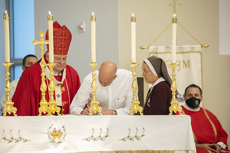 Having taken on a new name, Father Joseph Mary of the Priestly, Pierced and Eucharistic Heart of Jesus signs the Formula of Profession as Archbishop Thomas Wenski and Mother Adela Galindo, foundress of the Servants of the Pierced Hearts of Jesus and Mary, look on.