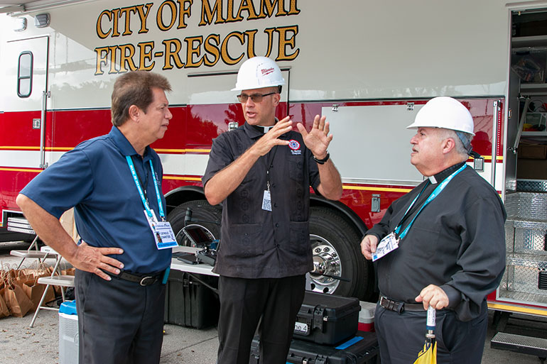 Father Christopher Marino, center, rector of St. Mary Cathedral and chaplain to City of Miami Fire Rescue, speaks with Peter Routsis-Arroyo, left, and Father Juan Sosa, pastor of St. Joseph, Miami Beach, after visiting the site of the collapsed Champlain Towers South the afternoon of July 2, 2021.