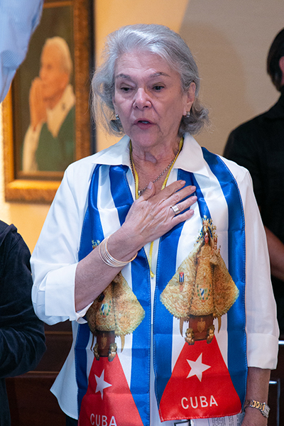 Conchita Gutierrez of Little Flower Parish in Coral Gables sings the Cuban national anthem at the start of a Mass for Cuba celebrated by Archbishop Thomas Wenski at the Shrine of Our Lady of Charity on on July 13, 2021, two days after anti-government protests broke out all over the island.