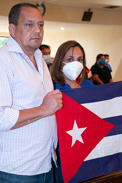 Pedro Camacho and Marta Trujillo of St. Hugh Parish in Coconut Grove hold a Cuban flag as Archbishop Thomas Wenski celebrates a Mass for Cuba at the Shrine of Our Lady of Charity on July 13, 2021, two days after anti-government protests broke out all over the island.