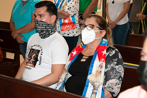 Wearing a T-shirt with a Marian image and a scarf with the Cuban flag and the country's patroness, people take part in a Mass for Cuba celebrated by Archbishop Thomas Wenski at the Shrine of Our Lady of Charity on July 13, 2021, two days after anti-government protests broke out all over the island.
