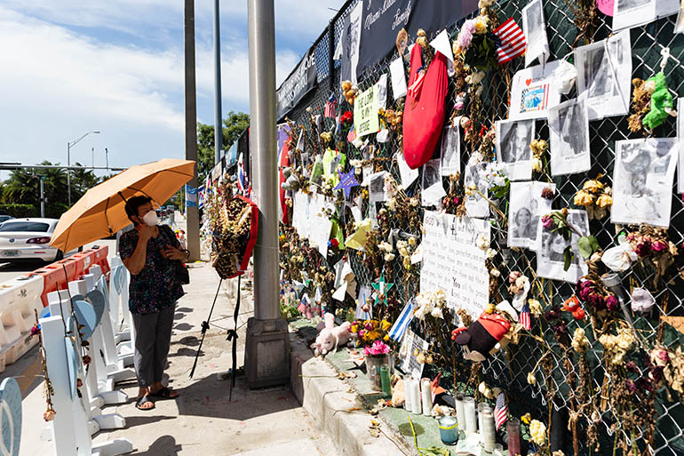 """A woman looks at the ever-evolving """"wall of remembrance"""" that commemorates the lives of the 97 victims identified so far in the June 24, 2021 tragedy."""