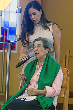 Silvana Marmolejos holds the microphone for her grandmother, Reina Marmolejos, 95, as she recites the rosary prior to the Mass for the World Day for Grandparents and the Elderly at St. Thomas University, July 25, 2021. Miami Auxiliary Bishop Enrique Delgado celebrated the special Mass at the university's St. Anthony Chapel.