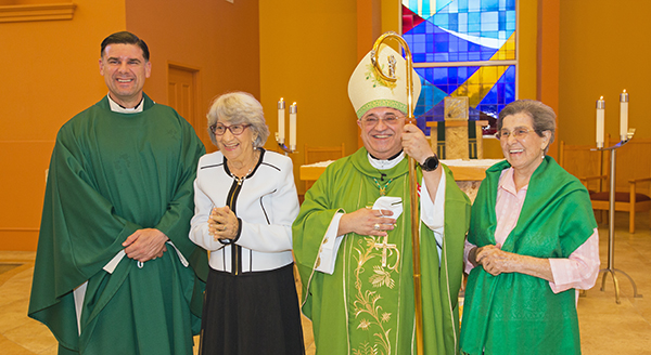 Father Rafael Capo, vice president of Mission and Ministry at St. Thomas University, poses with Sofia Ruiz, Miami Auxiliary Bishop Enrique Delgado, and Reina Marmolejos after the Mass July 25, 2021, to mark the first World Day for Grandparents and the Elderly. Bishop Delgado celebrated the  Mass at St. Thomas University's St. Anthony Chapel.