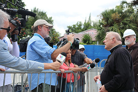 Archbishop Thomas Wenski speaks to the press July 2, 2021, after visiting the site of the partially collapsed Champlain Towers South in Surfside. He was accompanied on the visit, at right, by Boston Cardinal Sean Patrick O'Malley.
