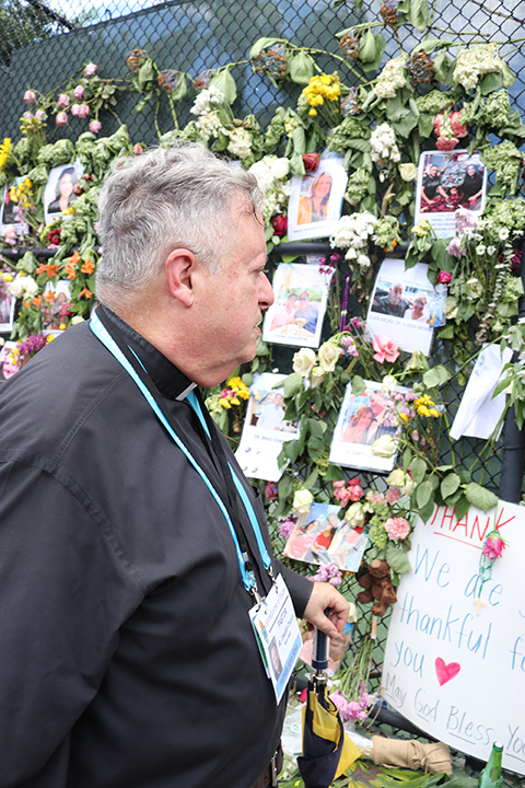 Father Juan Sosa, pastor of St. Joseph Church, Miami Beach, pays a visit July 2, 2021 to the memorial wall for the victims of the Champlain Towers South collapse in Surfside, a number of whom were members of his parish.