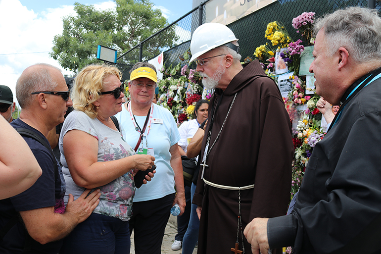 Boston Cardinal Sean Patrick O'Malley speaks with the mother of Anastacia Gramova, one of those missing in the collapse of the Champlain Towers South condominium in Surfside, during a July 2, 2021 visit to the memorial wall located near the collapse site. At center is Martha Lohrstorfer, a volunteer counselor with the Red Cross.