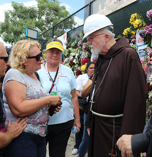 Martha Lohrstorfer, a Red Cross volunteer and Catholic from Michigan, center, stands and listens as a woman looking for her missing daughter speaks with Boston Cardinal Sean O'Malley during his July 2, 2021 visit to the site of the Champlain Towers South collapse.