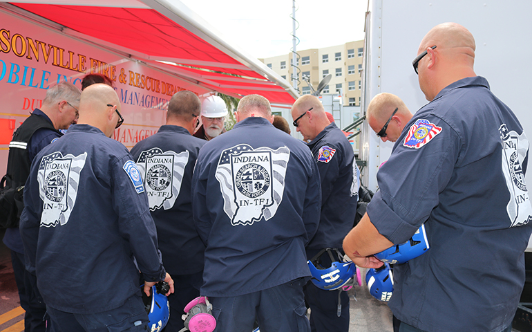 Boston Cardinal Sean Patrick O'Malley prays with members of an Indiana search and rescue team during a July 2, 2021 visit to the site of the partially collapsed Champlain Towers South condominium.