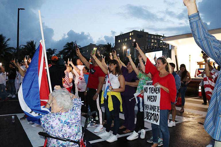 Decenas de cubanos de la diáspora que acudieron al santuario de la Ermita de la Caridad, en Miami, el 14 de julio, para orar por Cuba, levantan sus teléfonos celulares con las luces encendidas mirando a Cuba.