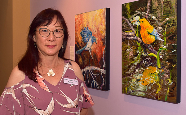 MaiYap, founder of the Palette Knife Artists of Miami, shows Lorraine Tucker's painting of a Florida scrub jay, left, and her picture of a prothonotary warbler.