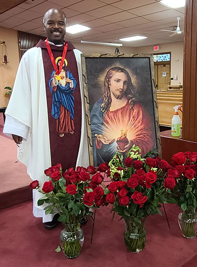 Father Patrick Charles, pastor of St. Stephen Parish in Miramar, displays an image of the Sacred Heart at his parish, which now has a small army of Guards of Honor. He is spiritual director for the parish association.
