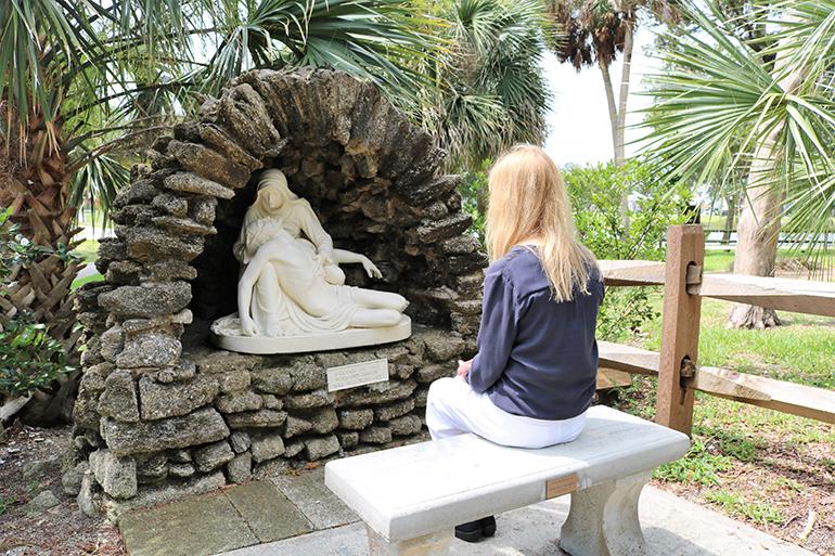 La reportera Linda Reeves reza frente a una de las estatuas en los terrenos de la Misión de Nombre de Dios, en San Agustín, que es también el sitio del Santuario de Nuestra Señora de La Leche.