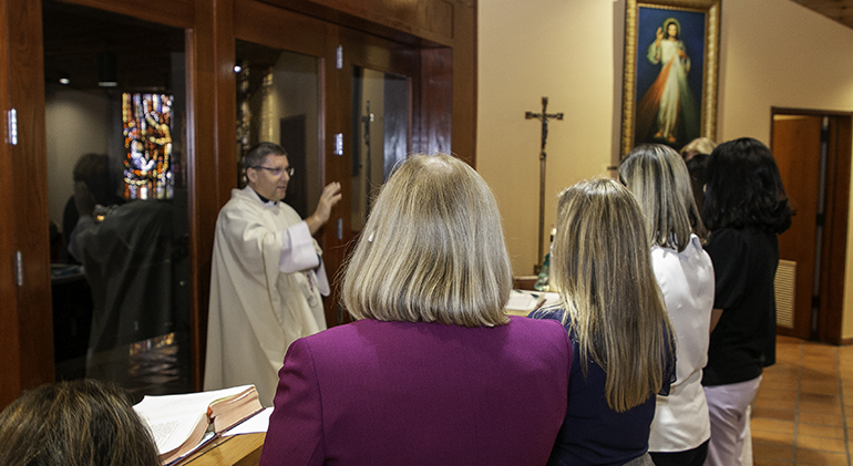 New principals receive a blessing from Msgr. Dariusz J. Zielonka of the Metropolitan Tribunal at the conclusion of Mass during their orientation day, July 29, 2021. The archdiocese's new superintendent of schools, Jim Rigg, welcomed a cohort of eight new principals and two second-year principals to the orientation session at the Pastoral Center. The new principals also spent some time with veteran principals who have been assigned to them as mentors.