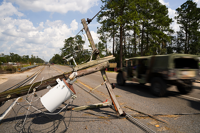 A vehicle passes downed power lines on Sept. 1, 2021 in Albany, Louisiana, one of the parts of Louisiana where Ida made landfall as a Category 4 hurricane Aug. 29, 2021, bringing flooding, wind damage and power outages along the Gulf Coast. (Photo by Sean Rayford/Getty Images)