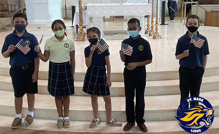 St. Mark students hold up flags to mark Patriots Day, this year leading up to the 20th anniversary of the Sept. 11 attacks. Students at the Southwest Ranches school wore red, white, and blue accessories with their uniforms Sept. 8, 2021.