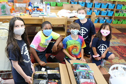 Fourth-graders pack boxes with donations collected as part of a drive at St. Ambrose School in Deerfield Beach for the observance of the 20th anniversary of the Sept. 11 attacks.