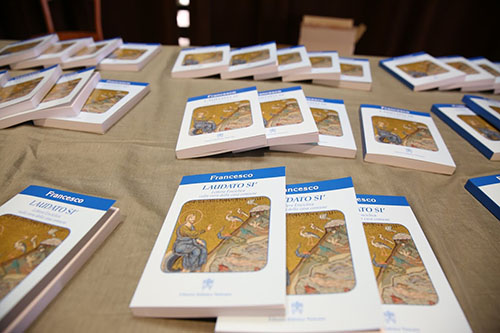 """Copies of Pope Francis' encyclical """"Laudato Si"""" are shown at a press conference in Paul VI Hall in Vatican City on the day it was released, June 18, 2015. The name of the encyclical is taken from St. Francis of Assisi's medieval Italian prayer """"Canticle of the Sun."""" The encyclical addresses the environment, climate change, abortion, embryonic experimentation, and population control."""