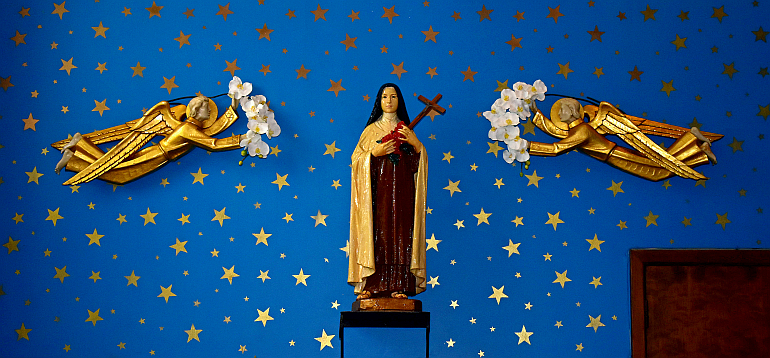 St. Therese of Lisieux, the church's patron, stands in a starry sky with angels offering flowers at Little Flower Church in Hollywood.