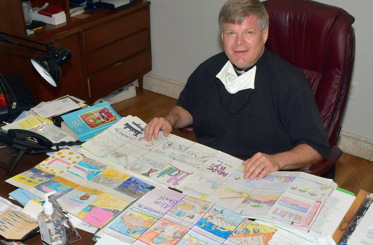 """Father Steven O'Hala shows some of the 80 storyboards produced by St. David School students as part of an awareness campaign on the plight of Haiti. """"I was blown away,"""" he said."""