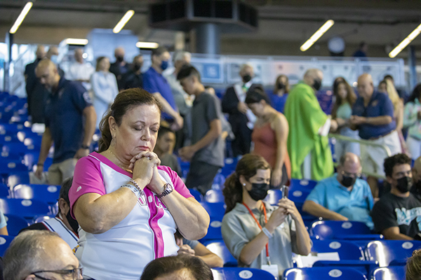 """Luz Spinola prays after receiving Communion, during the first ever """"Mass at the Park"""" celebrated at LoanDepot Park in Miami, Oct. 3, 2021."""