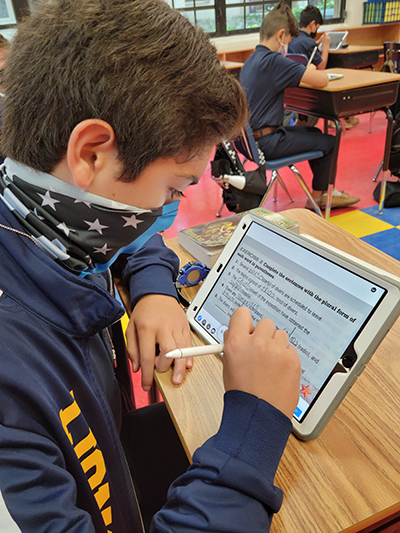 A middle school student from St. Mark School works on an English lesson from his iPad.