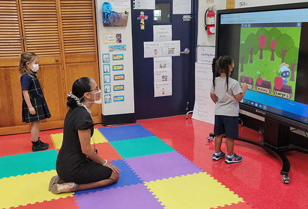 PreK3 students from St. Mark School show Principal Teresita Wardlow how they work and solve problems on a smart board in the classroom. St. Mark's has been named a 2021 Apple Distinguished School for their innovation, leadership and educational excellence.