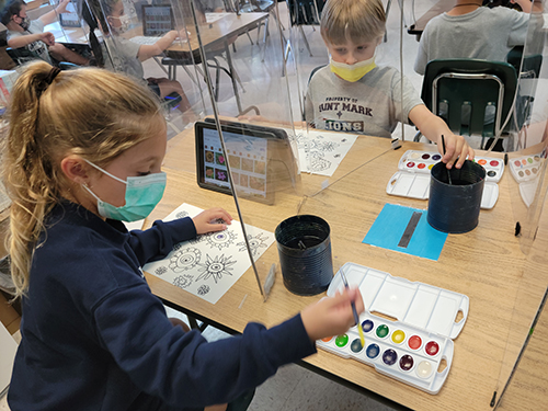 Artistic inspiration and iPads: St. Mark students check in on their color palette and flower styles during a water color lesson. Their art teacher, Carol Powers, incorporates a hands-on water color art lesson with visuals found on student iPads.