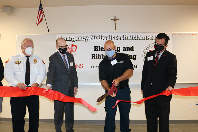 Omar Jirau, a 1995 graduate of Cardinal Gibbons High School and Emergency Medical Technician instructor for the school and Barry University in Miami Shores, cuts the ribbon during ceremonies Sept. 24, 2021 at the Fort Lauderdale school.