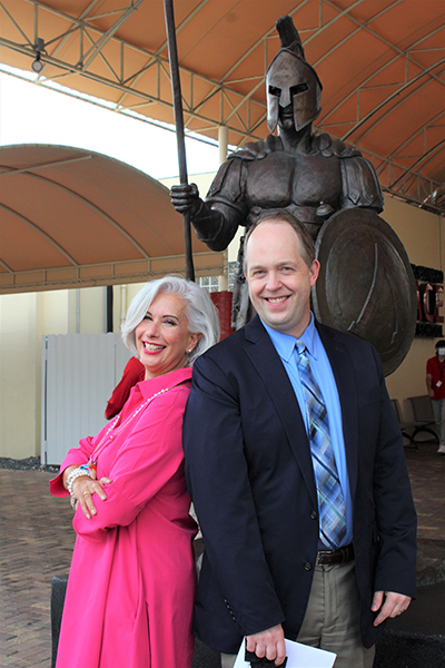 Msgr. Edward Pace High School alum and principal, Ana Garcia, and Archdiocese of Miami Superintendent of Schools Jim Rigg pose in front of the school's Spartan statue. The school is celebrating 60 years since its doors first opened in the Archdiocese of Miami.