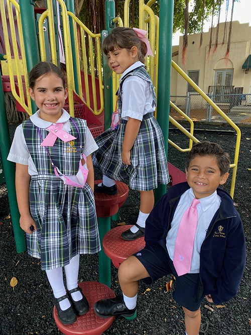 St. Theresa School second grader Annelise Cortinas, kindergartener Camila Vidal and second grader Jacob Cruz look pretty in pink for Breast Cancer Awareness Month.